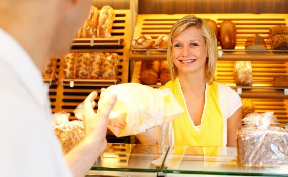 19291641 - bakery shopkeeper hands bag of bread over to customer